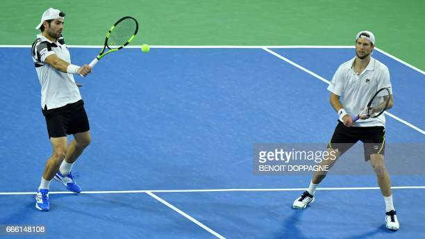 Italy's Simone Bolelli and Andreas Seppi return the ball during the Davis Cup World Group quarterfinal between Belgium and Italy on April 8 in...