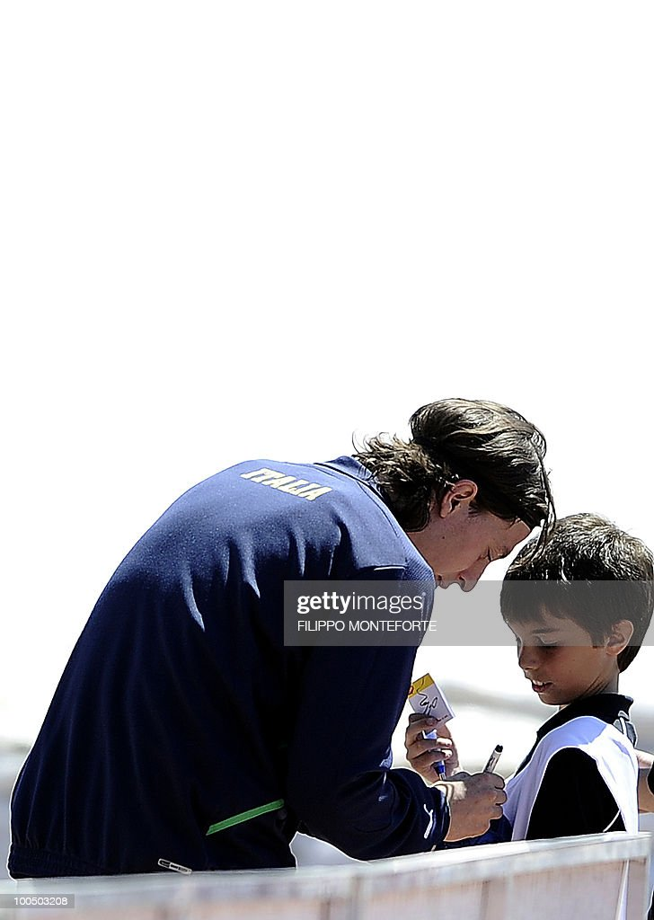 Italy's soccer team's midfielder Riccardo Montolivo (L) signs an autograph to a young supporter during a training session in Sestriere on May 25, 2010. The Italian team started today a retreat in the mountains of Sestriere before the FIFA World Cup 2010 in South Africa. AFP PHOTO / Filippo MONTEFORTE