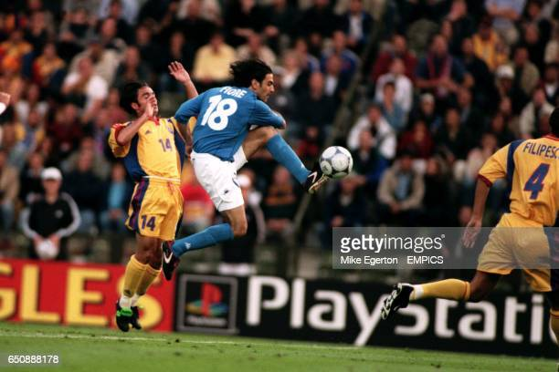 Italy's Stefano Fiore shoots toward goal under pressure from Romania's Florentin Petre