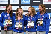 Italy's team members celebrate with their gold medals on the podium after winning the women's 4x200m Freestyle final of the 32nd LEN European...