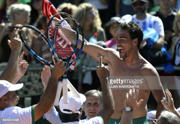 Italy's tennis player Fabio Fognini waves his jersey celebrating with teammates after defeating Argentina's Guido Pella 26 46 63 64 62 during their...