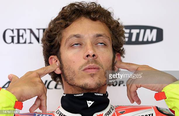 Italy's Valentino Rossi of Ducati Team puts on earplugs before the third training session of the MotoGP of Germany at the Sachsenring Circuit on July...