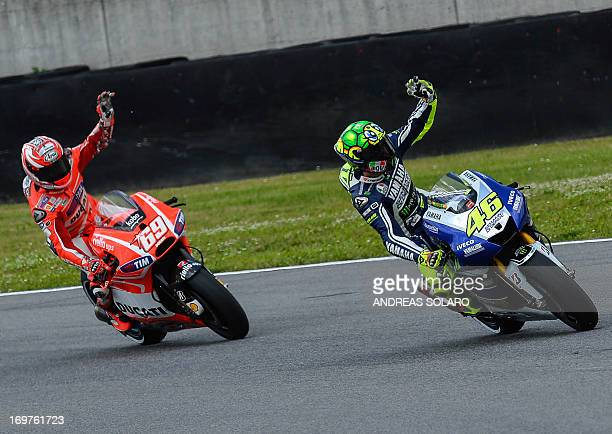 Italy's Valentino Rossi waves to spectators as he rides his Yamaha ahead of US Nicky Hayden of Ducati at the end of a qualification session on June 1...