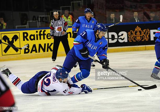 Italy's Vincent Rocco and Great Britain's Robert Dowd vie for the puck during the 2013 IIHF Ice Hockey World Championship Division I Group A match...