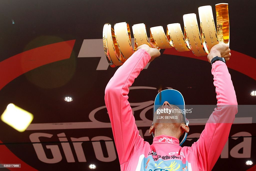 Italy's Vincenzo Nibali celebrates with the trophy on the podium after winning the 99th Giro d'Italia, Tour of Italy, after the 21th stage from Cuneo to Turin on May 29, 2016. Astana's Vincenzo Nibali secured his second Giro d'Italia triumph on Sunday after topping a dramatic 99th edition that saw key rival Steven Kruijswijk agonisingly crash during the final stages. Germany's Nikias Arndt, of the Giant team, celebrated winning the final stage into Turin although it came only after Giacomo Nizzolo, of the Trek team, was stripped of the victory by race judges who ruled the Italian had hampered other riders by deviating from his sprint line. / AFP / Luk BENIES