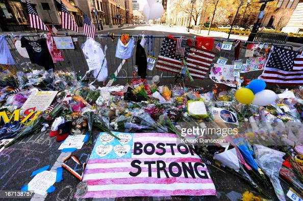 Items are placed by people visiting a makeshift memorial for victims near the site of the Boston Marathon bombings at the intersection of Boylston...
