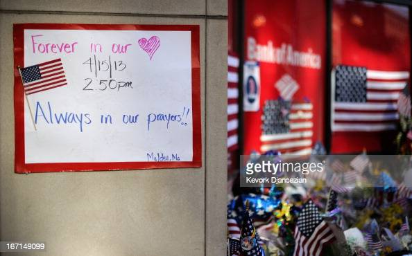 Items are placed by people visiting a makeshift memorial for victims near the finish line of the Boston Marathon bombings at the intersection of...