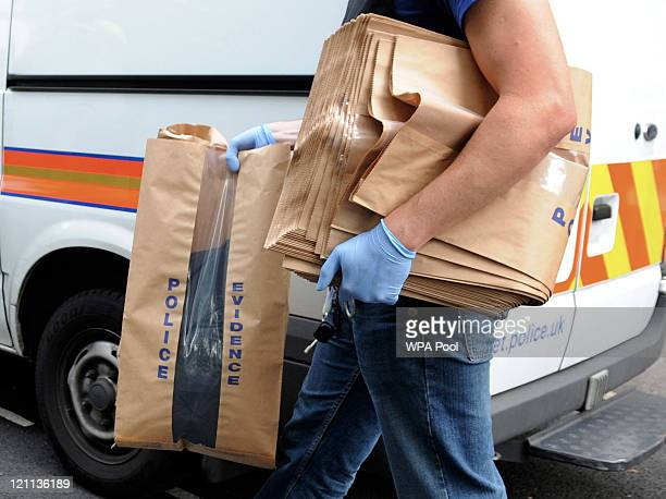 Items are removed in evidence bags by Metropolitan Police officers during an early morning raid at a property on Villa Road Brixton where a 17 year...