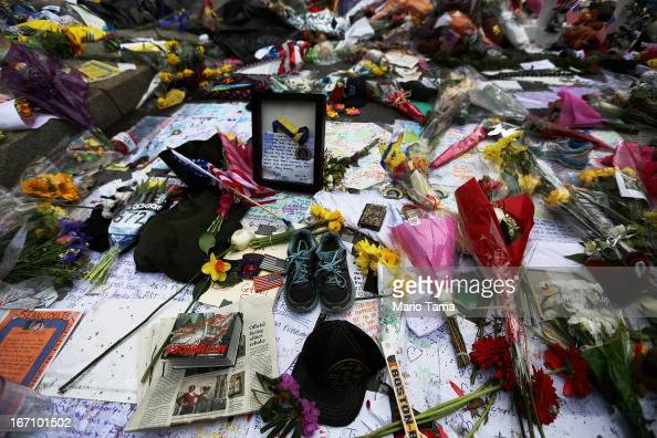 Items including a pair of running shoes have been placed at a makeshift memorial for victims near the site of the Boston Marathon bombings a day...