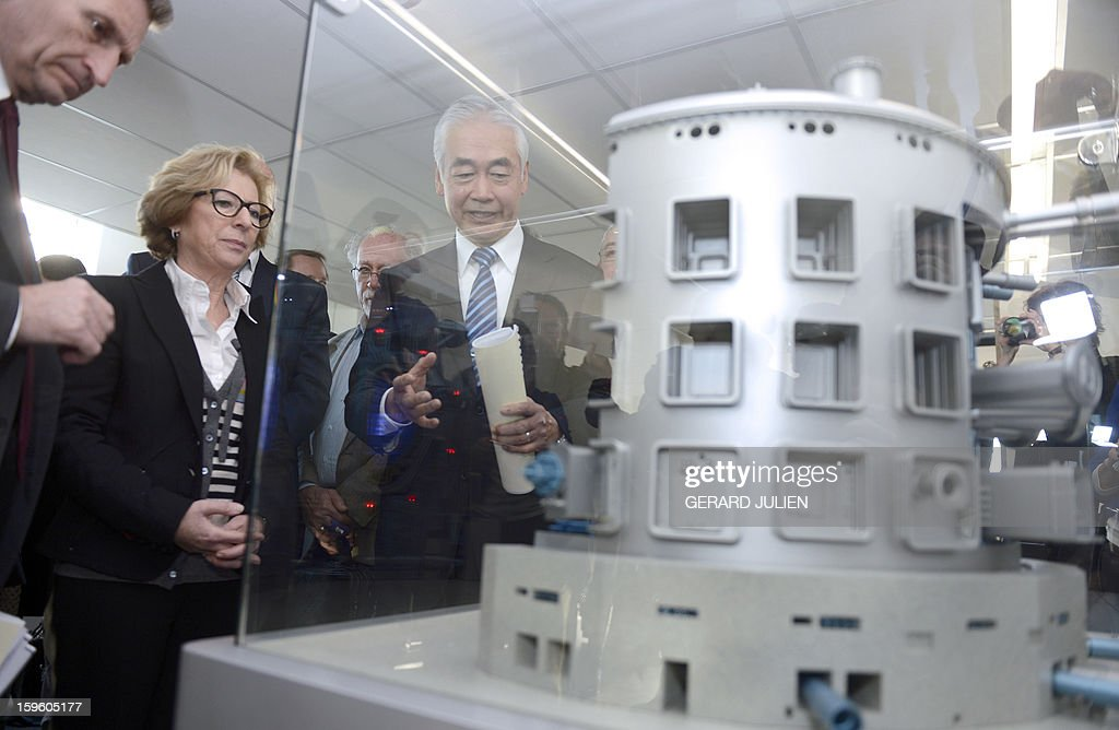 Iter organization's general director Osamu Motojima (R) presents to Guenther Oettinger (L), EU Commissioner for Energy and French minister for Higher Education and Research Genevieve Fioraso (C), the model of the reactor of the future International Thermonuclear Experimental Reactor (ITER) during the inauguration of the Iter Organization headquarters on January 17, 2013 in Saint-Paul-lez-Durance, southern France. The International Thermonuclear Experimental Reactor (Iter), based at the French Atomic Energy Commission (CEA) research center of Cadarache in Saint-Paul-lès-Durance, was set up by the EU, which has a 45 percent share, China, India, South Korea, Japan, Russia and the US to research a clean and limitless alternative to dwindling fossil fuel reserves.