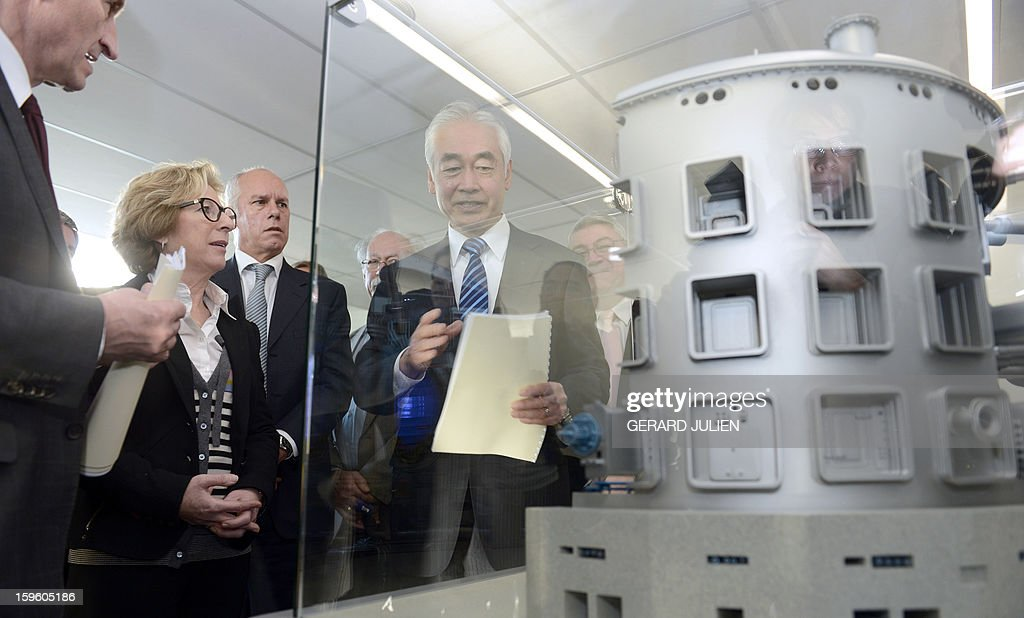 Iter organization's general director Osamu Motojima (R) presents to Guenther Oettinger (L), EU Commissioner for Energy and French minister for Higher Education and Research Genevieve Fioraso (C), the model of the reactor of the future International Thermonuclear Experimental Reactor (ITER) during the inauguration of the Iter Organization headquarters on January 17, 2013 in Saint-Paul-lez-Durance, southern France. The International Thermonuclear Experimental Reactor (Iter), based at the French Atomic Energy Commission (CEA) research center of Cadarache in Saint-Paul-lès-Durance, was set up by the EU, which has a 45 percent share, China, India, South Korea, Japan, Russia and the US to research a clean and limitless alternative to dwindling fossil fuel reserves. AFP PHOTO / GERARD JULIEN