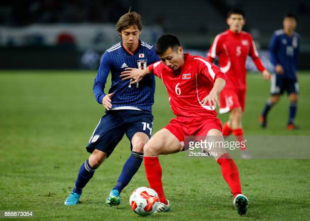 Ito Junya of Japan and Kang Kuk Chol of North Korea in action during the EAFF E1 Men's Football Championship between Japan and North Korea at...