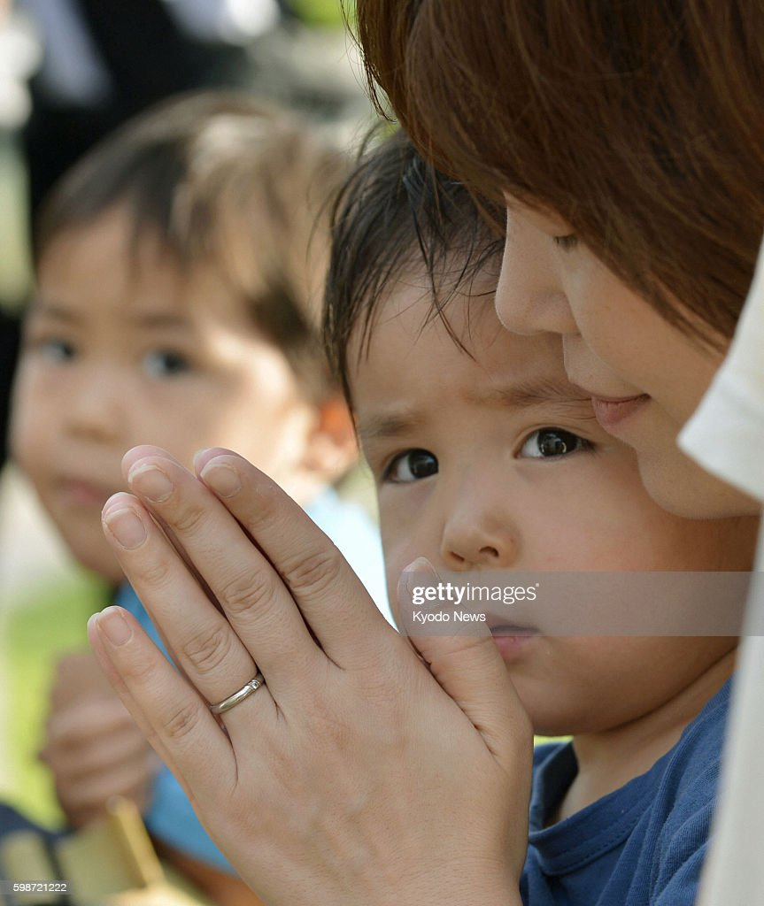 Itoman Japan A woman with a child prays at the Cornerstone of Peace monument in Itoman Okinawa Prefecture on June 23 2012 Okinawa marked the 67th...