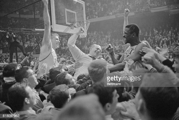 It's a jubilant mob scene as happy fans carry Celtics' Tommy Heinsohn coach Red Auerbach and big Bill Russell around the basketball court at Boston...