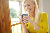 Shot of a beautiful young woman enjoying a hot drink next to a window at home