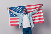 It's my native country! Portrait of cheerful glad excited confident with toothy beaming smile student wearing denim casual outfit holding flag of the USA isolated on gray background