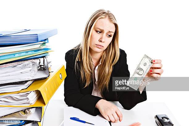 It's not enough: sad overworked businesswoman  with single dollar bill