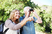 Positive senior couple using some binoculars while out on a hike