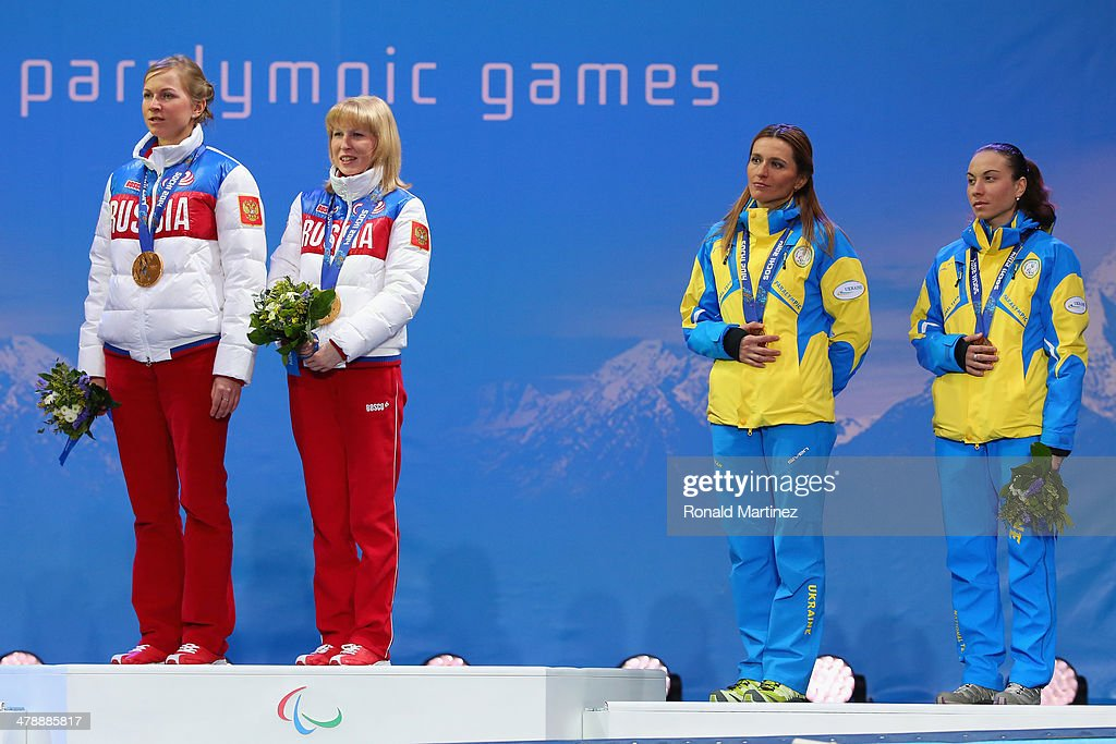 Iuliia Budaleeva of Russia (R) and guide Tatiana Maltseva (L) sing the national anthem as bronze medalists guide Lada Nesterenko and Oksana Shyshkova of the Ukraine cover thir medals at the medal ceremony for the the Women's 12.5km Visually Impaired Biathlon on day eight of the Sochi 2014 Paralympic Winter Games at Laura Cross-country Ski & Biathlon Center on March 15, 2014 in Sochi, Russia.