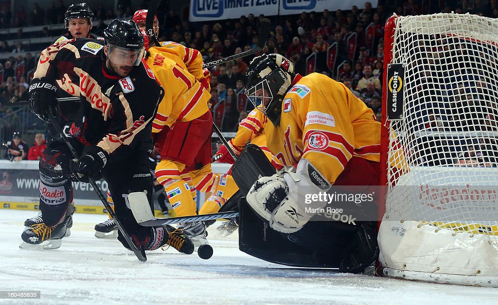 Iva Ciernik (L) of Hannover fails to score over Felix Bick (R), goaltender of Duesseldorf during the DEL match between Hannover Scorpions and Duesseldorfer EG at TUI Arena on February 1, 2013 in Hanover, Germany.