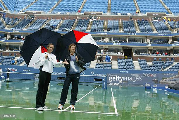 Iva Majoli of Croatia and Daniela Hantuchova of Slovakia pose for photographers as rain suspends play during the US Open at the United States Tennis...