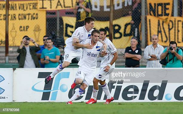 Ivan Alonso of Nacional celebrates with his teammaates after scoring the first goal of his team during a match between Penarol and Nacional as part...