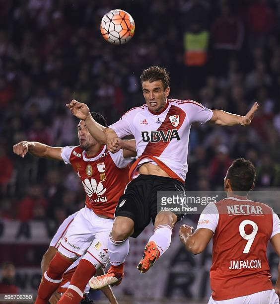 Ivan Alonso of River Plate fights for the ball with Horacio Salaberry of Independiente Santa Fe during a second leg match between River Plate and...