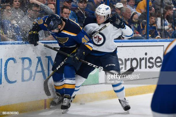 Ivan Barbashev of the St Louis Blues and Nelson Nogier of the Winnipeg Jets battle for the puck on April 4 2017 at Scottrade Center in St Louis...