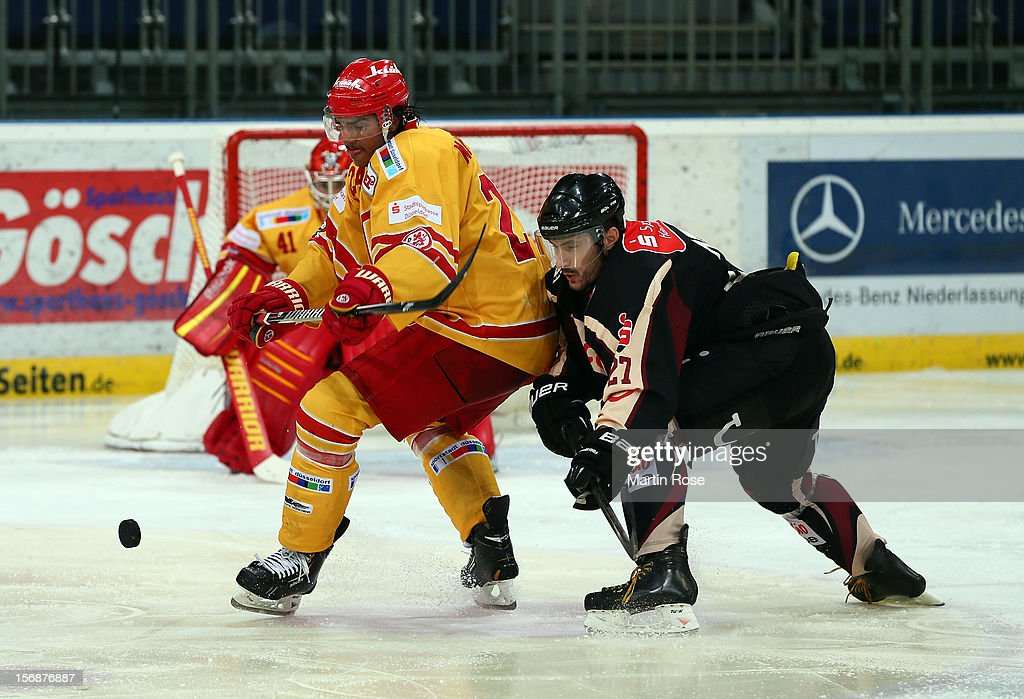 Ivan Ciernik (R) of Hannover and Andreas Martinsen (L) of Duesseldorf battle for the puck during the DEL match between Hannover Scorpions and Duesseldorfer EG at TUI Arena on November 23, 2012 in Hanover, Germany.