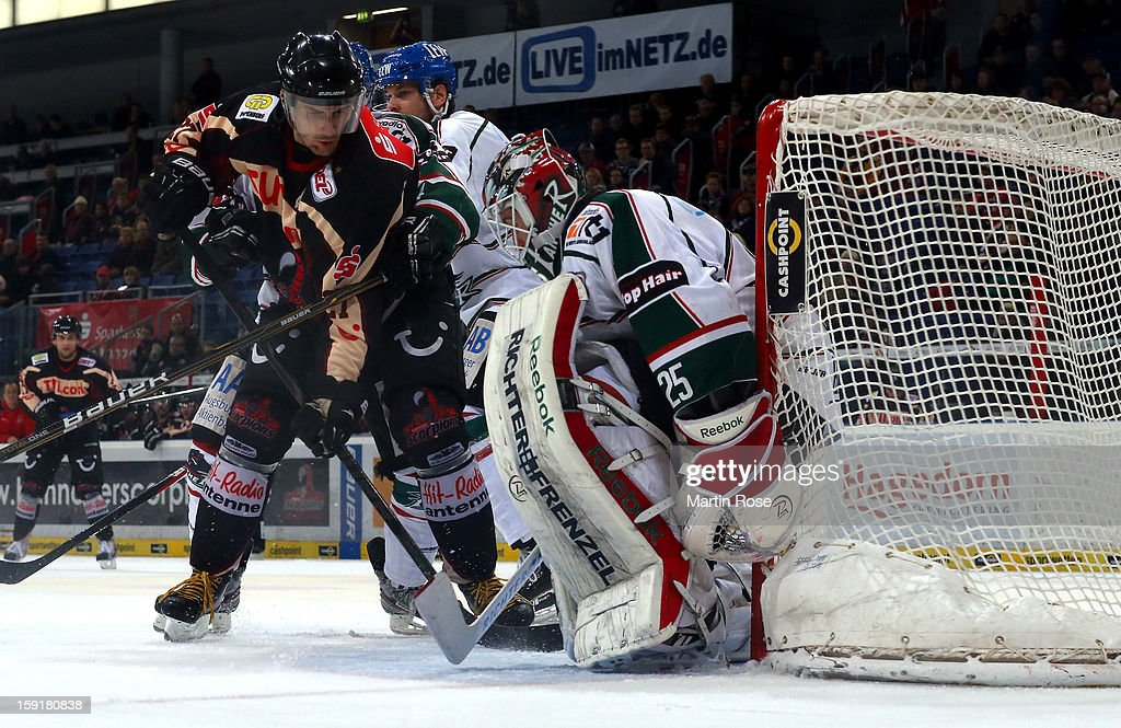 Ivan Ciernik (L) of Hannover and Justin Forrest(R) of Augsburg battle for the puck in front of the net during the DEL match between Hannover Scorpions and Augsburger Panther at TUI Arena at TUI Arena on January 9, 2013 in Hanover, Germany.