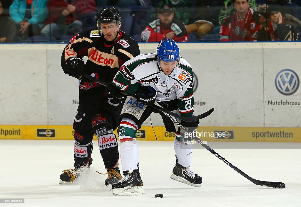 Ivan Ciernik (L) of Hannover and Peter MacArthur (R) of Augsburg battle for the puck during the DEL match between Hannover Scorpions and Augsburger Panther at TUI Arena at TUI Arena on January 9, 2013 in Hanover, Germany.