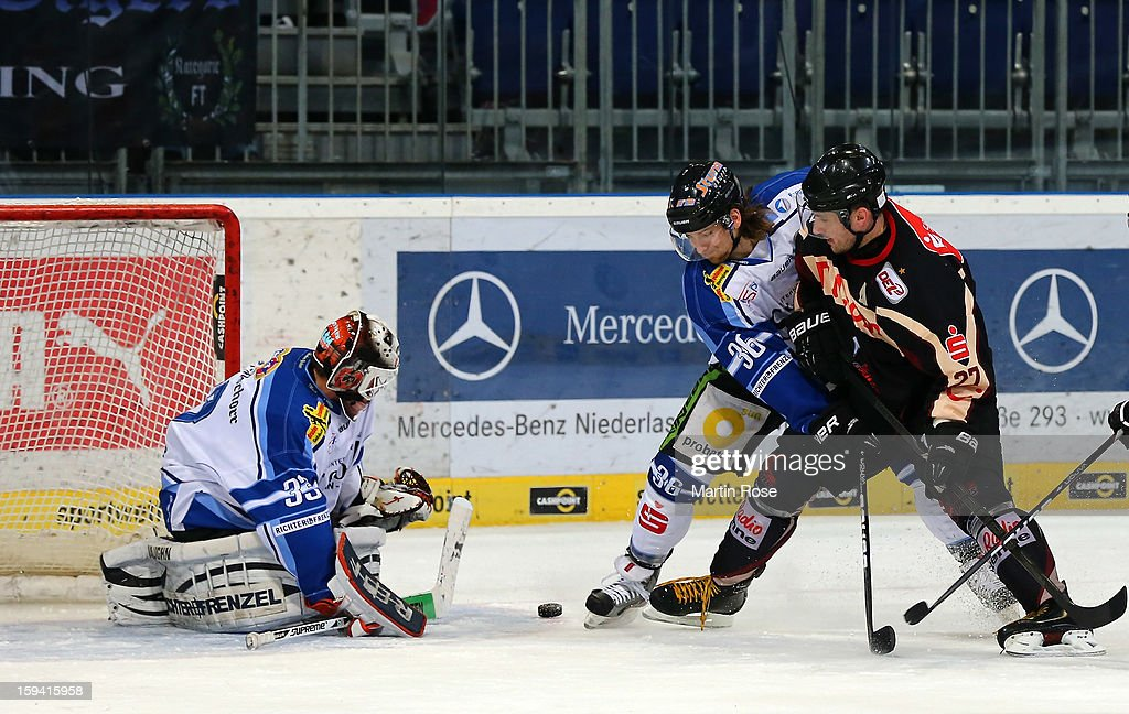 Ivan Ciernik (#27) of Hannover and Rene Kramer (#36) of Straubing battle for the puck during the DEL match between Hannover Scorpions and Straubing Tigers at TUI Arena on January 13, 2013 in Hanover, Germany.