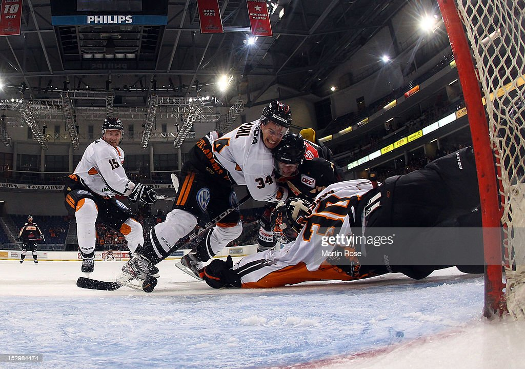 Ivan Ciernik of Hannover battles for the puck with Daniar Dshunussow goaltender of Wolfsburg during the DEL match between Hannover Scorpions and...