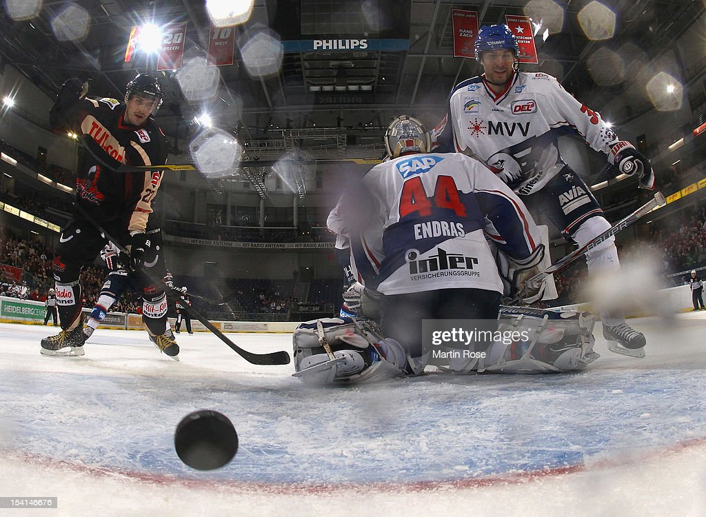 Ivan Clernik (L) of Hannover scores over <a gi-track='captionPersonalityLinkClicked' href=/galleries/search?phrase=Dennis+Endras&family=editorial&specificpeople=5526366 ng-click='$event.stopPropagation()'>Dennis Endras</a> (C), goaltender of Mannheim during the DEL match between Hannover Scorpions and Adler Mannheim at TUI Arena on October 14, 2012 in Hanover, Germany.