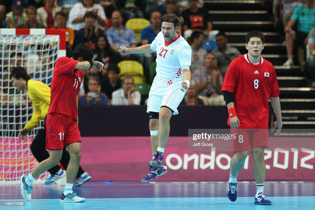 Ivan Cupic of Croatia celebrates a point while Duk-Jun Lim (L) and Junggeu Park (R) of Korea look dejected during the Men's Handball preliminaries group B match between Croatia and Korea on Day 2 of the London 2012 Olympic Games at the Copper Box on July 29, 2012 in London, England.