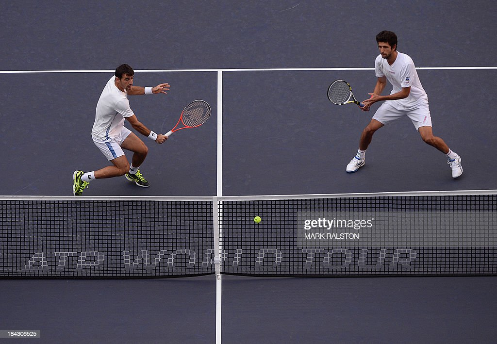 Ivan Dodig of Croatia (L) and Marcelo Melo of Brazil (R) play a shot before defeating David Marrero and Fernando Verdasco of Spain during their men's doubles finals at the Shanghai Masters 1000 tennis tournament held in the Qizhong Tennis Stadium in Shanghai on October 13, 2013. Dodig and Melo went on to win 7-6, 6-7, 1(10)-0 (2). AFP PHOTO /Mark RALSTON