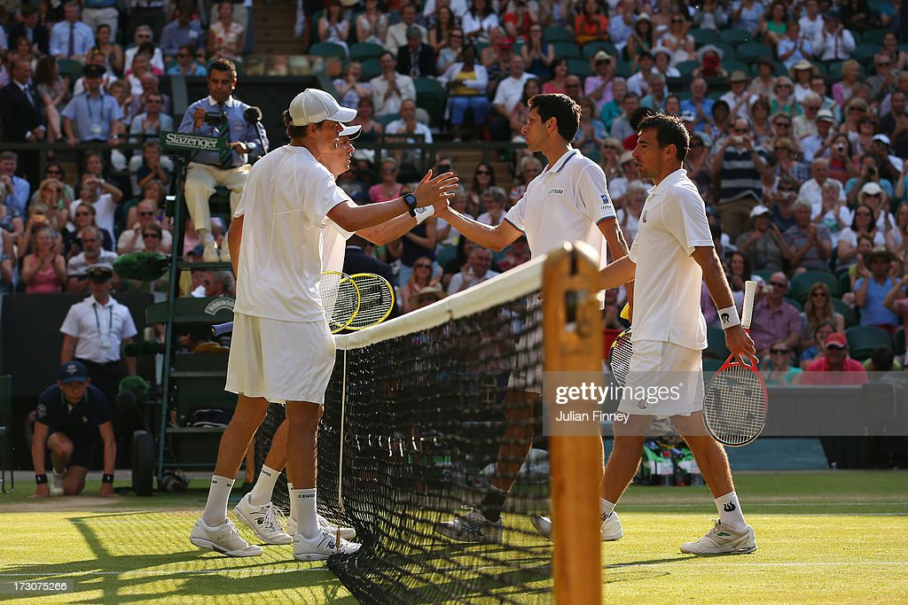 Ivan Dodig of Croatia and Marcelo Melo of Brazil shake hands at the net with Mike Bryan and Bob Bryan of the United States of America after their Gentlemen's Doubles final match on day twelve of the Wimbledon Lawn Tennis Championships at the All England Lawn Tennis and Croquet Club on July 6, 2013 in London, England.