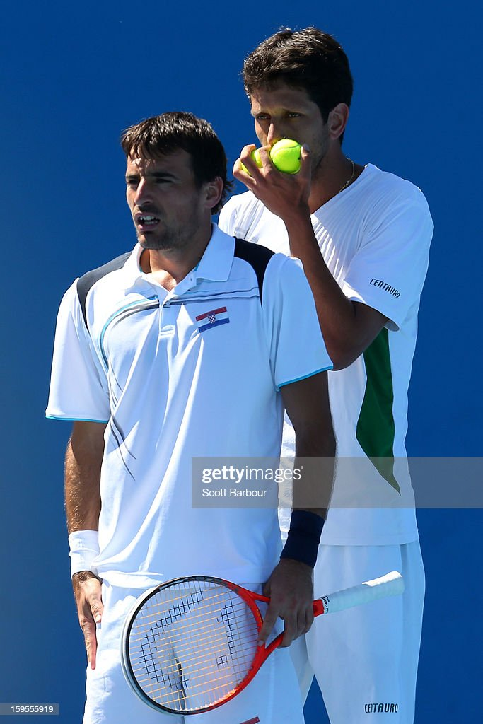 Ivan Dodig of Croatia and Marcelo Melo of Brazil talk tactics in their first round men's doubles match against Daniele Bracciali of Italy and Lukas Dlouhy of the Czech Republic during day three of the 2013 Australian Open at Melbourne Park on January 16, 2013 in Melbourne, Australia.