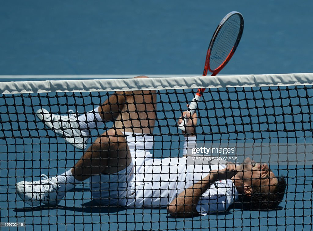 Ivan Dodig of Croatia falls on the court after playing a return during his men's singles match against France's Richard Gasquet on the sixth day of the Australian Open tennis tournament in Melbourne on January 19, 2013.