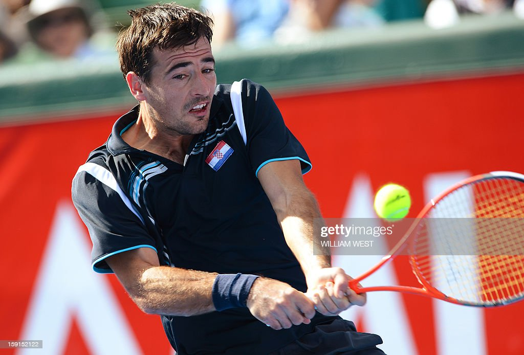 Ivan Dodig of Croatia hits a backhand return to Tomas Berdych of the Czech Republic at the Kooyong Classic tennis tournament in Melbourne on January 9, 2013. Top male players are using the round-round invitational tournament as a warm up to the Australian Open tennis tournament which runs January 14-27. AFP PHOTO/William WEST IMAGE