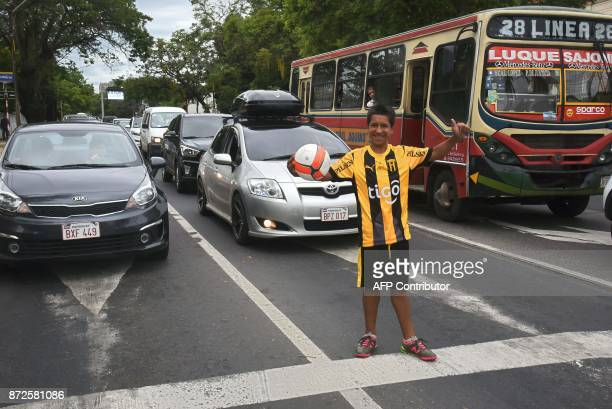 Ivan Genes performs pirouettes with a football in front of motorists stopped at a traffic light in Asuncion on November 10 2017 Two days after a...