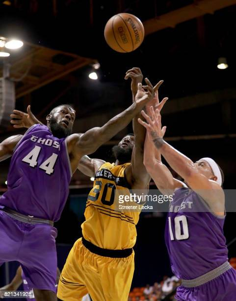 Ivan Johnson and Mike Bibby of the Ghost Ballers battle for a loose ball against Reggie Evans of the Killer 3s during week five of the BIG3 three on...