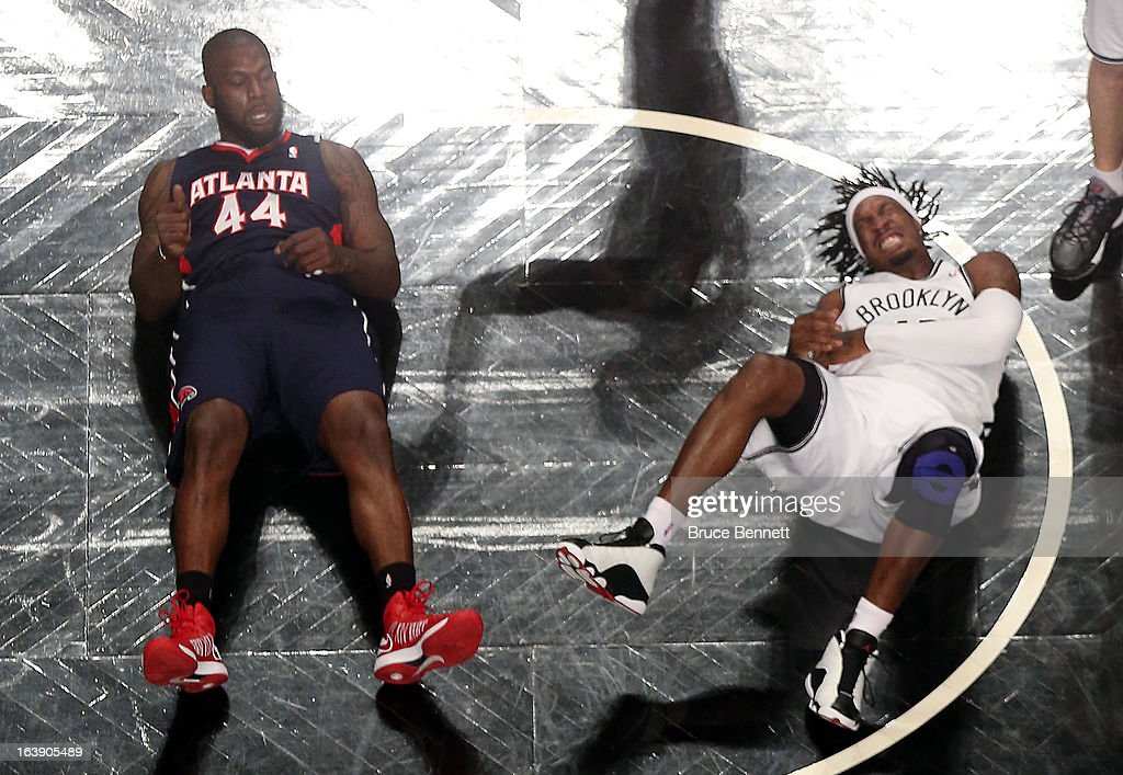 Ivan Johnson #44 of the Atlanta Hawks and Gerald Wallace #45 of the Brooklyn Nets hit the floor after colliding at the Barclays Center on March 17, 2013 in New York City. The Hawks defeated the Nets 105-93.NOTE