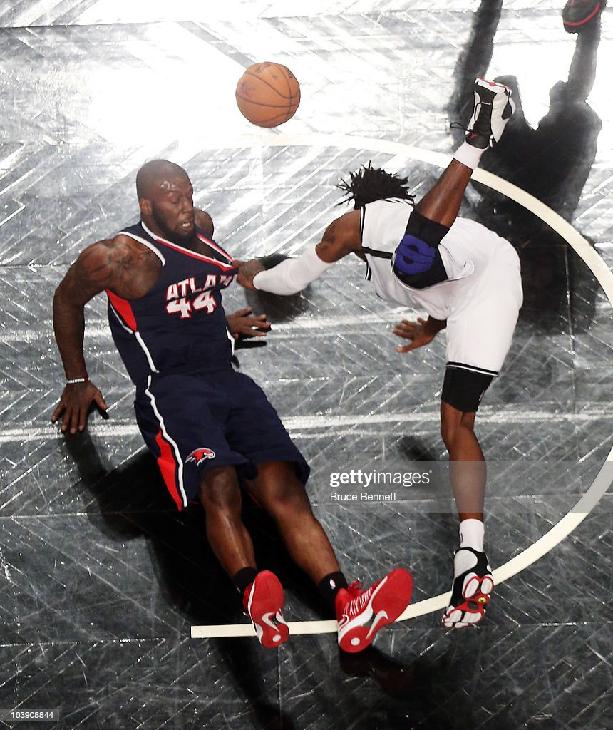 Ivan Johnson #44 of the Atlanta Hawks and <a gi-track='captionPersonalityLinkClicked' href=/galleries/search?phrase=Gerald+Wallace&family=editorial&specificpeople=202117 ng-click='$event.stopPropagation()'>Gerald Wallace</a> #45 of the Brooklyn Nets hit the floor after colliding at the Barclays Center on March 17, 2013 in New York City. The Hawks defeated the Nets 105-93.NOTE
