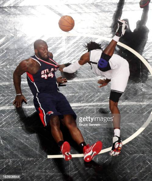 Ivan Johnson of the Atlanta Hawks and Gerald Wallace of the Brooklyn Nets hit the floor after colliding at the Barclays Center on March 17 2013 in...
