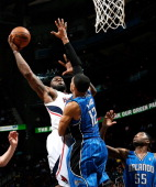 Ivan Johnson of the Atlanta Hawks attacks the basket against Tobias Harris and E'Twaun Moore of the Orlando Magic at Philips Arena on March 30 2013...