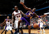 Ivan Johnson of the Atlanta Hawks battles for a rebound against Antawn Jamison of the Los Angeles Lakers at Philips Arena on March 13 2013 in Atlanta...
