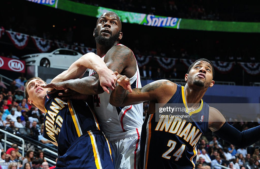 Ivan Johnson #44 of the Atlanta Hawks battles for a rebound against Tyler Hansbrough #50 and Paul George #24 of the Indiana Pacers during Game Four of the Eastern Conference Quarterfinals in the 2013 NBA Playoffs on April 29, 2013 at Philips Arena in Atlanta, Georgia.