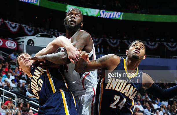 Ivan Johnson of the Atlanta Hawks battles for a rebound against Tyler Hansbrough and Paul George of the Indiana Pacers during Game Four of the...