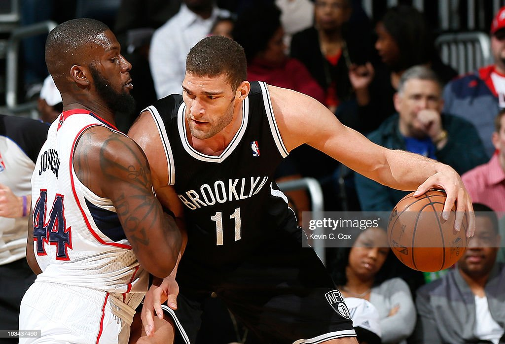 Ivan Johnson #44 of the Atlanta Hawks defends against <a gi-track='captionPersonalityLinkClicked' href=/galleries/search?phrase=Brook+Lopez&family=editorial&specificpeople=3847328 ng-click='$event.stopPropagation()'>Brook Lopez</a> #11 of the Brooklyn Nets at Philips Arena on March 9, 2013 in Atlanta, Georgia.
